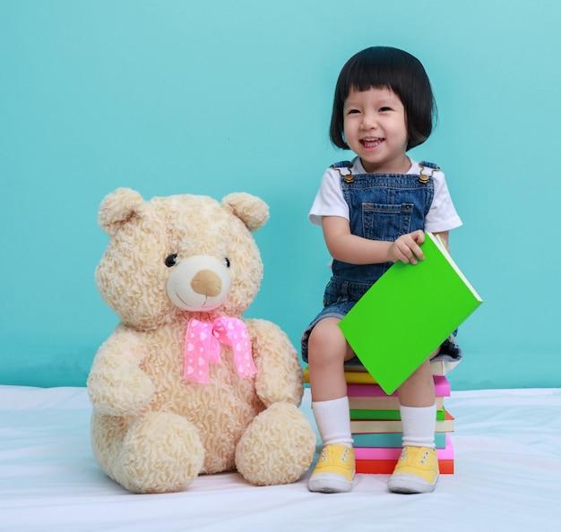 Kind kleines mädchen oder ein kleines süßes mädchen, das ein buch liest und auf den büchern mit einem spielzeug sitzt