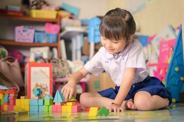 Kind kleines mädchen spielen spielzeug unordentlich chaos im wohnzimmer einen schmutzigen oder unordentlichen zustand von spielzeug und puppe zu hause.
