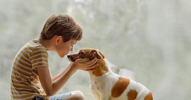Kind küsst den hund in der nase am fenster.
