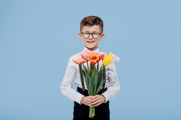 Kind lächelnder kleiner junge mit brille, die sie blumen übergeben. , isoliert auf blauer wand