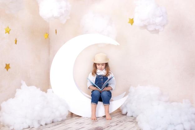 Kind lernt im kindergarten lesen. kleines mädchen, das auf mond mit wolken und sternen sitzt. kleines mädchen liest mit buch in ihren händen. kind träumt.