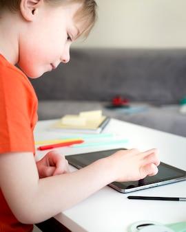 Kind lernt neue informationen vom digitalen tablet