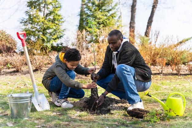 Kind lernt, wie man einen baum pflanzt
