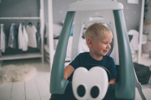 Kind liegt auf dem boden. junge spielt zu hause morgens im haus mit spielzeugautos. lässiger lebensstil im schlafzimmer.