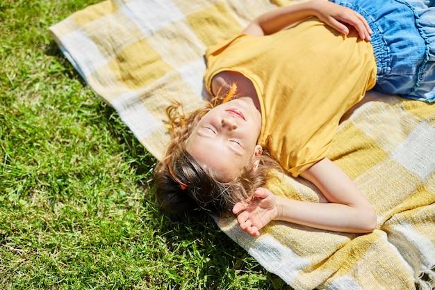 Kind liegt auf der decke, auf dem gras am sonnentag, kleines mädchen nimmt ein sonnenbad im hinterhofhaus