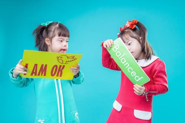 Kind liest nachricht. zwillingsschwestern bleiben zusammen mit plakaten in den händen und in kleidern