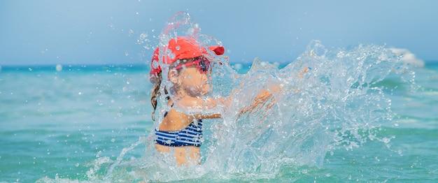 Kind macht spray auf dem meer.
