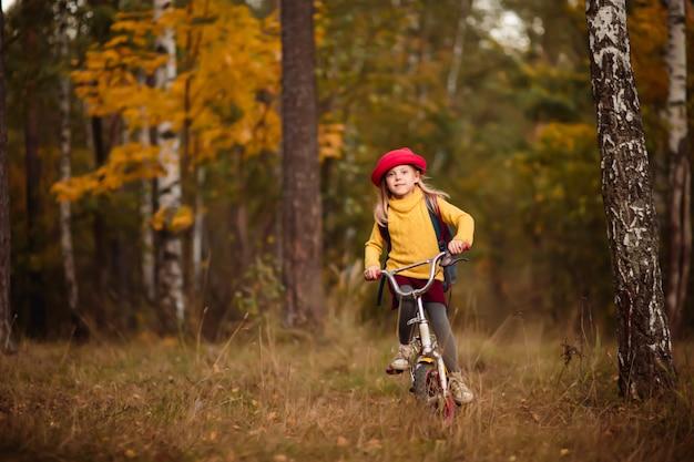 Kind, mädchen auf einem fahrrad in hellen kleidern und einem hut, im park im herbst