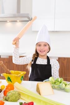 Kind mädchen chef auf der arbeitsplatte lustige geste mit rollenknete