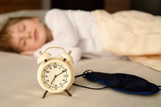 Kind mädchen, das in einem bett schläft. am frühen morgen wecker und schlafmaske im vordergrund.