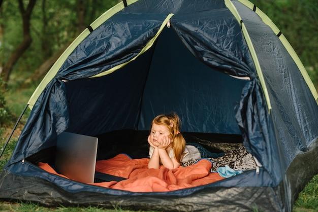 Kind mädchen in einer kampagne in einem zelt