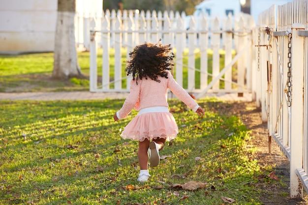 Kind mädchen kleinkind spielen im park hintere ansicht