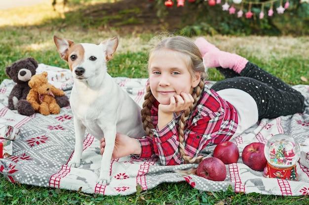 Kind mädchen mit hund jack russell terrier in der nähe des weihnachtsbaumes mit geschenken,