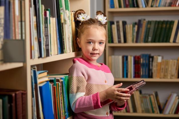 Kind mädchen mit pferdeschwänzen steht in der bibliothek nach dem unterricht, genießen es, erzogen zu werden, neue informationen und kenntnisse zu erhalten