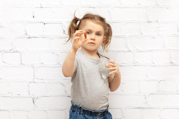 Kind mädchen mit pille auf der hand und glas wasser pillen und vitamine für kinder