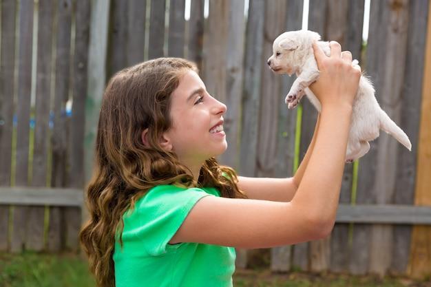 Kind mädchen mit welpen haustier chihuahua glücklich spielen