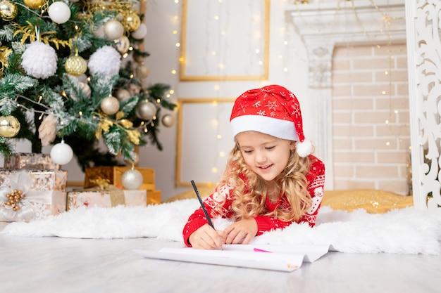 Kind mädchen schreibt einen brief an den weihnachtsmann am weihnachtsbaum