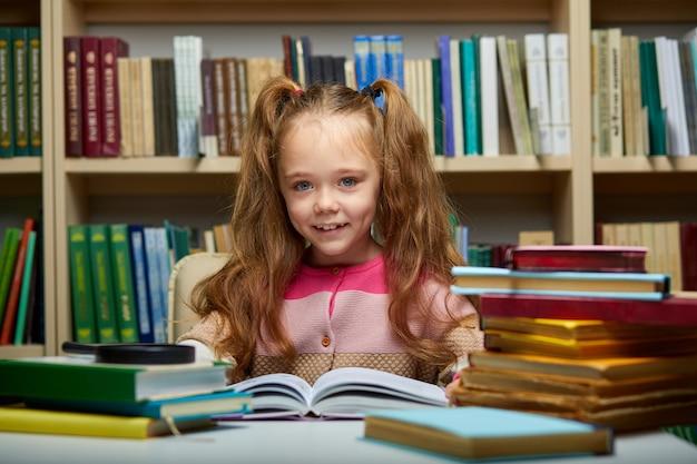 Kind mädchen sitzt mit büchern am tisch in der bibliothek, kind im buchladen, umgeben von bunten büchern für die schule, sie schaut in die kamera lächelnd