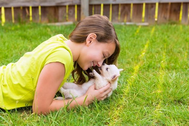 Kind mädchen und welpen hund glücklich im rasen liegen