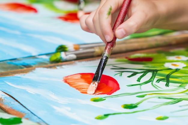 Kind malt ein bild durch gouache. kind, das mohnblumen und kamille zeichnet. die hand und pinsel