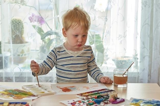 Kind malt mit farben auf einem blatt papier