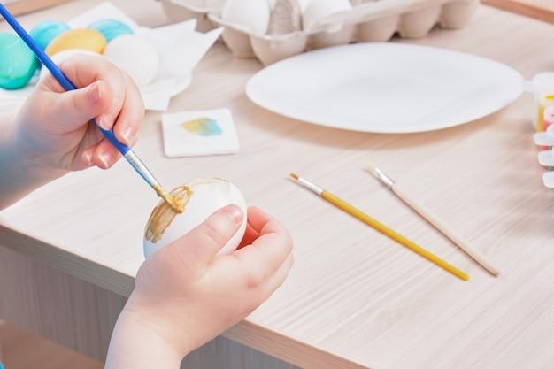 Kind malt osterei auf einem holztisch, eierkarton, teller, pinsel und malt auf dem tisch