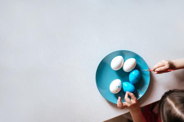Kind malt ostereier auf blauem teller, der am tisch sitzt nah oben kopienraum