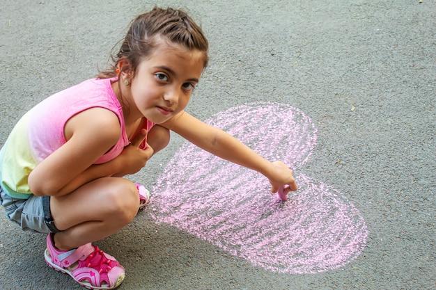 Kind malte mit kreide ein herz auf den asphalt. selektiver fokus.art