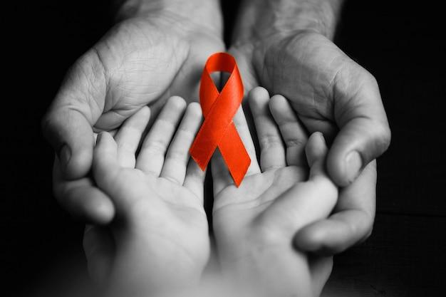 Kind mit aid rotem band. der junge hält das symbol des kampfes gegen hiv, aids. konzept der hilfe für bedürftige. schwarz und weiß.