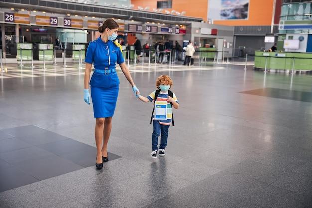 Kind mit ausweis, das mit einem kabinenpersonal kommt