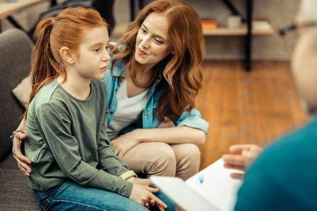 Kind mit autismus. nettes trauriges mädchen, das vor ihr schaut, während es an autismus leidet