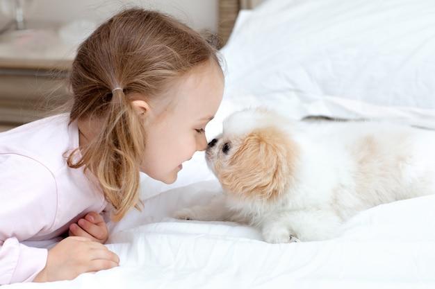 Kind mit baby-hund kinder spielen mit welpen zu hause tierpflege freundschaft zwischen haustier und kindern