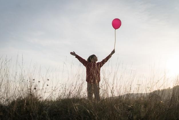 Kind mit ballon auf graswiese