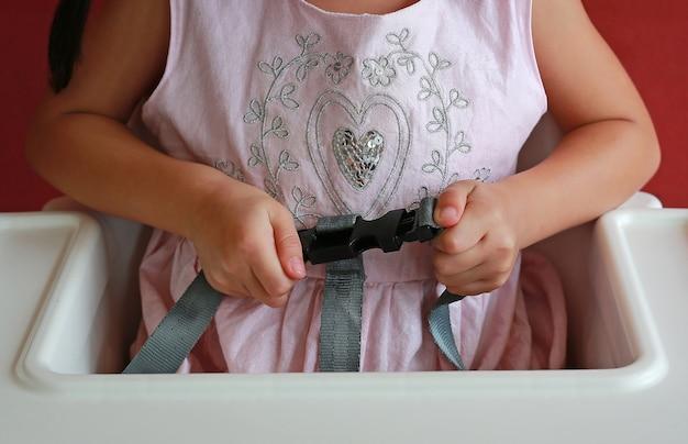 Kind mit befestigung sicherheitsgurt auf hochstuhl