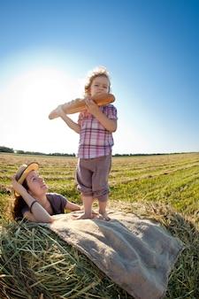 Kind mit brot, das auf hayrick im herbstweizenfeld steht gesundes lebensstilkonzept