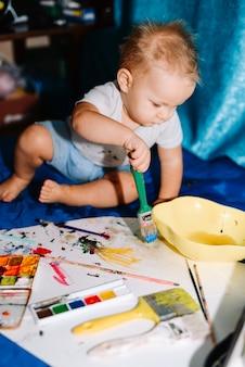 Kind mit bürstenmalerei auf papier nahe wasserfarben und sitzen auf bettdecke