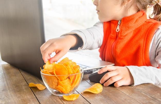 Kind mit chips hinter einem computer