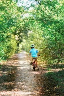 Kind mit dem fahrrad. scherzen sie in einem sturzhelm, der ein fahrrad im wald reitet.
