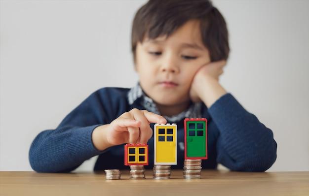 Kind mit dem traurigen gesicht, das neben stapel von geldmünzen sitzt