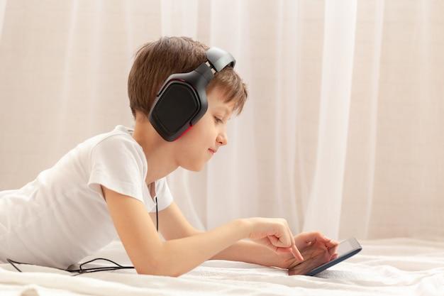 Kind mit digitalem tablet und laptop, das zu hause musik auf dem teppich hört. konzept online-bildung