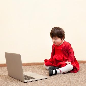 Kind mit down-syndrom beim betrachten des laptops