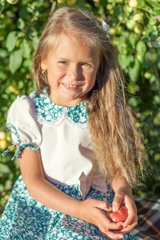 Kind mit einem apfel im garten. selektiver fokus. natur.