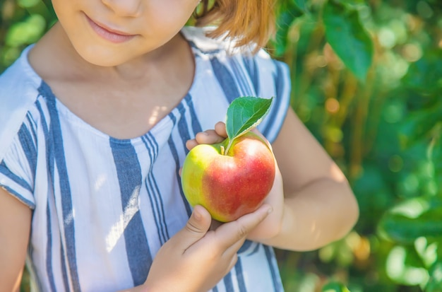 Kind mit einem apfel im garten