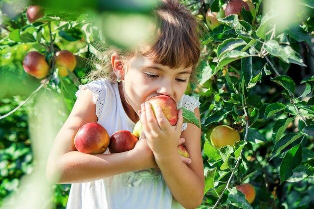 Kind mit einem apfel selektiver fokus garten.