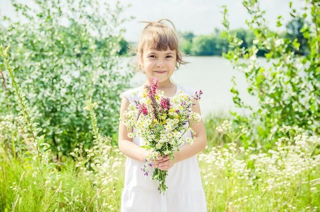 Kind mit einem blumenstrauß von wildblumen. tiefenschärfe. natur.