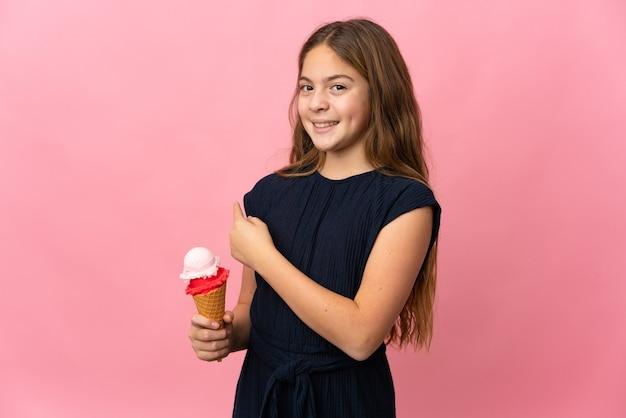 Kind mit einem kornett-eis über isoliertem rosa hintergrund, der nach hinten zeigt