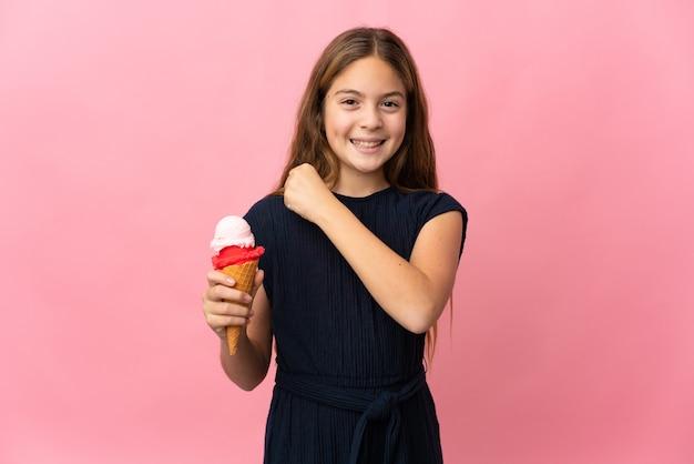 Kind mit einem kornett-eis über lokalisiertem rosa hintergrund, der einen sieg feiert