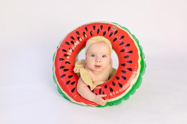 Kind mit einem schwimmring in form einer wassermelone liegt auf einem weißen isolierten hintergrund