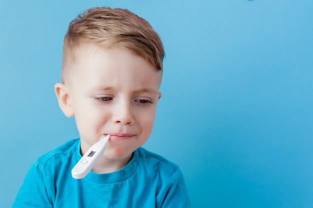 Kind mit einem thermometer im mund