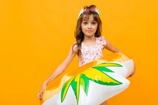 Kind mit einer baseballkappe in einem badeanzug mit einem ananasschwimmkreis auf einer gelben wand